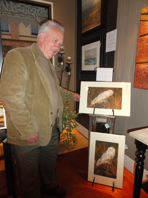 Neal Maine, NW naturalist and artist,  proudly showing photographs of the Artic snowy owls that have visited the North coast.