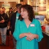 Artist Linda Trexler in bright ocean blue spoke to art patrons.