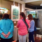 Hostess Linda-in blue- busy as always assisting art patrons.