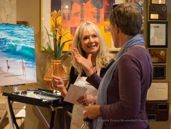 Artist Victoria Brooks engages an art patron.