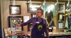 Artist Gretha Lindwood highlighting a work in progress while painting LIVE.